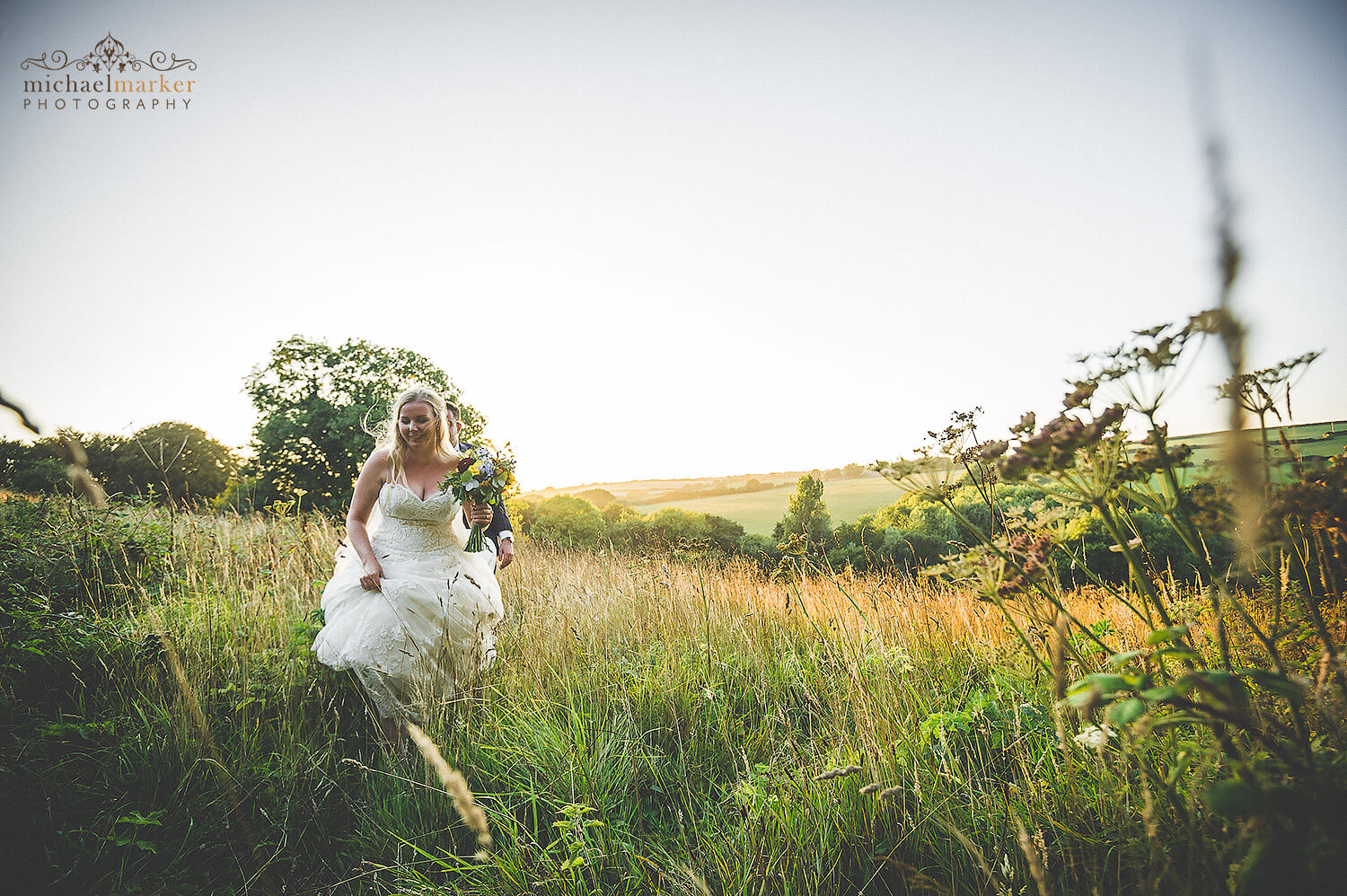 Bride and groom walk through flower meadow field back to wedding reception at Trevenna