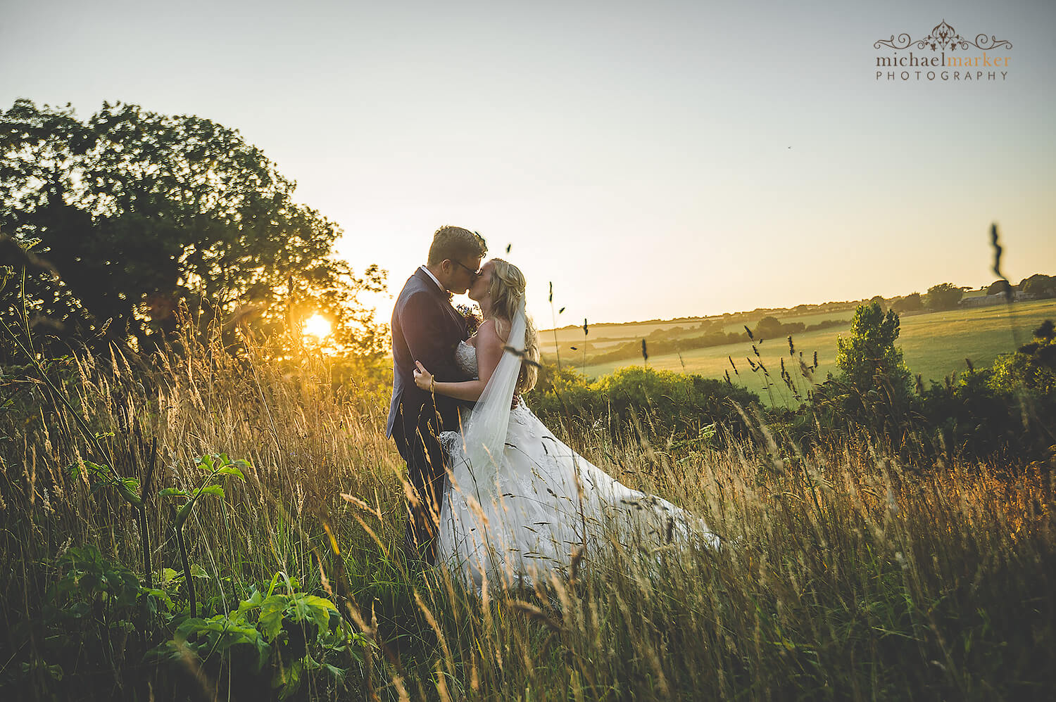 Bride and groom kiss at sunset in field at Trevenna Barns